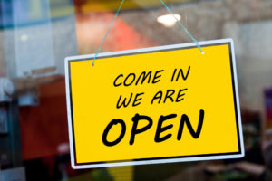 come in we are open sign hanging on a window door outside a local business trying to drive online customers in
