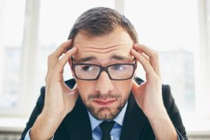 Frustrated businessman in eyeglasses touching his head because he doesn't have any followers on social media