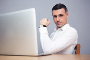 Businessman sitting at the table with laptop and looking at camera after writing awesome piece of marketing content
