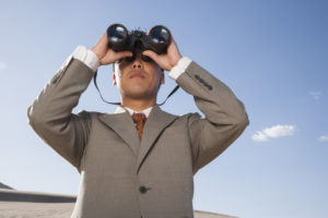 Businessman with binoculars looking to future of marketing