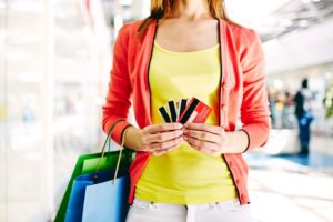 Female customer with plastic cards and shopping bags looking for local business