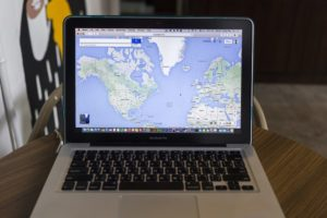 map of world on laptop for business owner looking to reach local customers