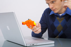 Man pointing gun at laptop because of bad website