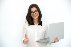 Smiling businesswoman standing with laptop and showing thumb up after reading positive review about company
