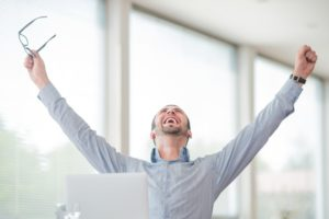 Victorious corporate man celebrating with his arms lifted in the air because he improved website SEO