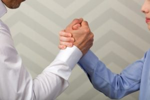 two people shaking hands and trusting each other