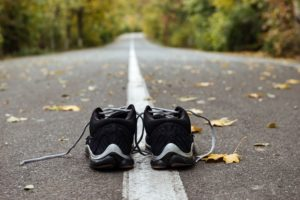 black running shoes on road like marketing marathon for local businesses