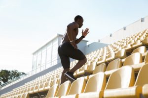 young man runner on a stadium running upstairs like overwhelmed business trying to follow marketing plan