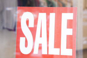 sale sign in business window trying to attract local customers with marketing