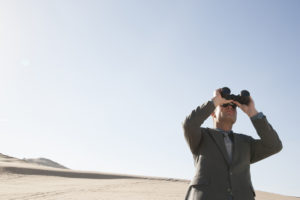 Businessman with binoculars looking into future